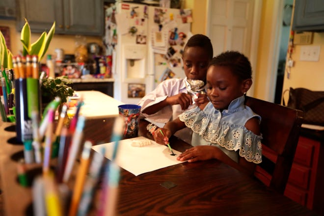 Neijal Nurse, 8, left, watches as his sister Ava Rose Nurse, 5, paints a picture their kitchen Wednesday, June 26, 2019.