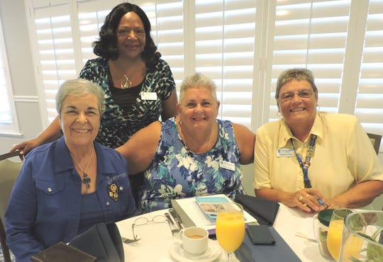 Eula Clarke, standing, with Marie Kennedy, seated, left, Paula Austin and Deborah Wilde at Soroptimist International of Stuart's Installation of Officers and Annual Retreat.