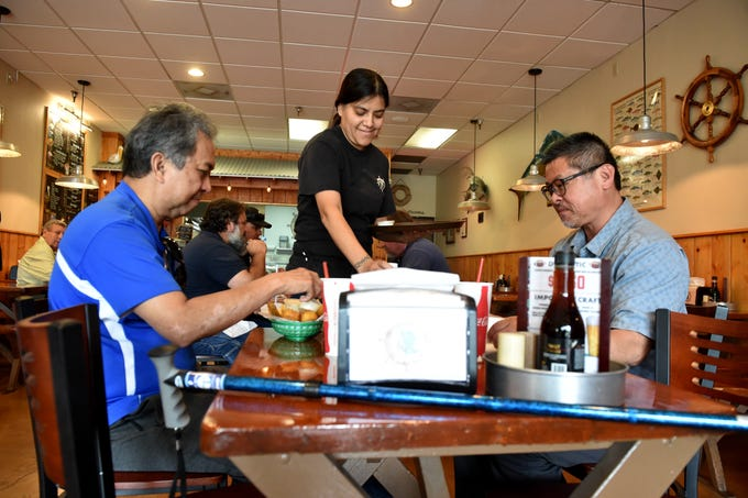 Griselda Orosco serves up fish and chips to Mel Algas, left, and Tim Jue during a lunch visit to Thousand Oaks Fish & Chips.