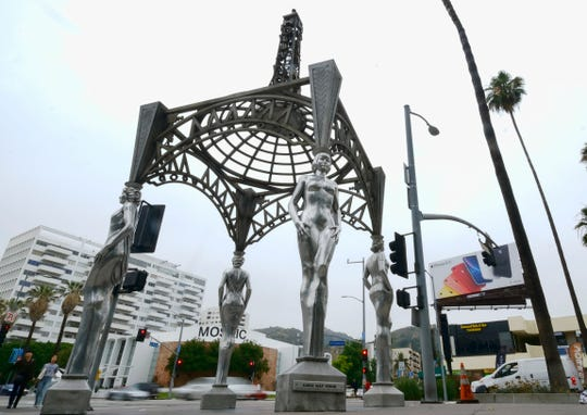 "Pedestrians walk past the ""Four Ladies of Hollywood"" gazebo on Hollywood Boulevard in Los Angeles on June 19.  Officials say someone climbed the more than two-story tall public art piece and stole a statue of Marilyn Monroe."
