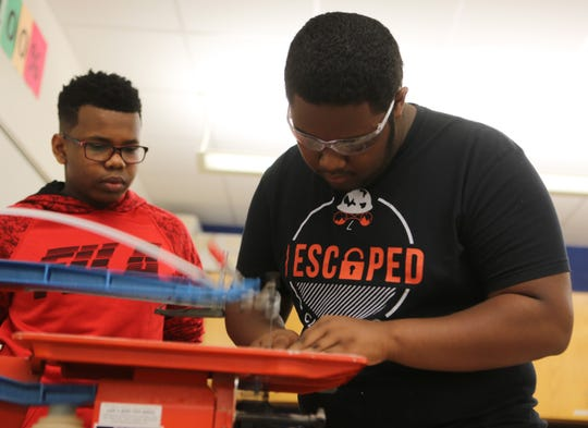 Kiyarre Earle-Blake uses a scroll saw for his solar car while Carl Martin looks on.  The boys, along with five other students, will represent Bayard Middle School at a technology conference this weekend in Washington D.C.