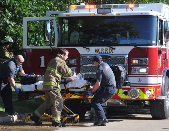 Wichita Falls emergency medical personnel rush  a child to an awaiting ambulance after being rescued from a burning house on Amber Avenue  Wednesday morning.