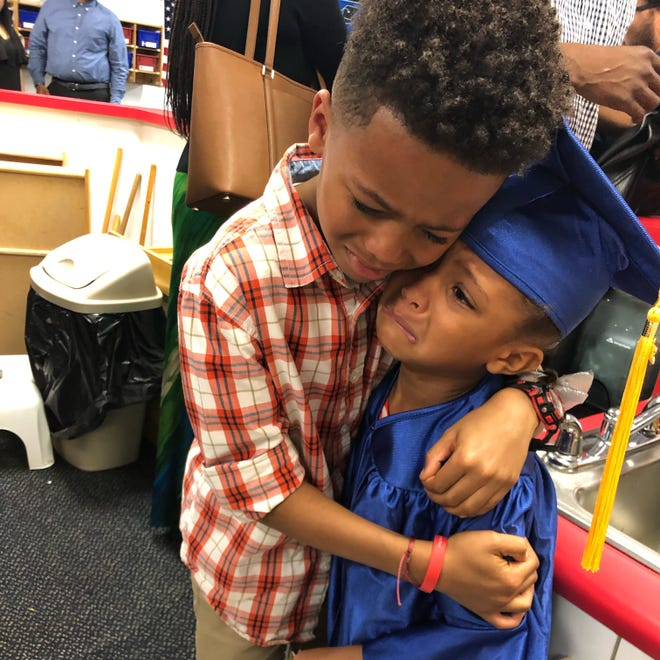 Derek Smith, 8, hugs his 5-year-old sister Charlee Smith, after Charlee's Pre-K graduation.