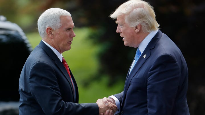 President Donald Trump shakes hands with Vice President Mike Pence, before walking across the South Lawn of the White House in Washington, May 19, 2017.