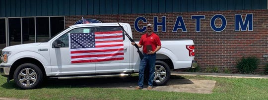 Koby Palmer, 29, poses with a truck, a bible, a shotgun and an American flag at Chatom Ford in Alabama.