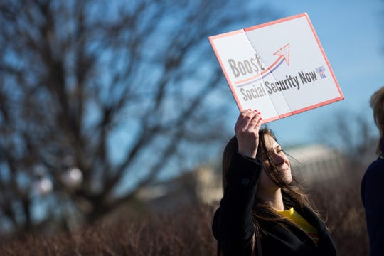 A participant holds up a sign as House Democrats hold a news conference to announce the introduction of Social Security 2100 Act in front of the U.S. capitol building in Washington, D.C. on March 18, 2015.