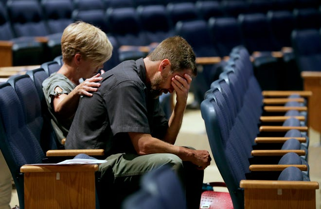 Kelly Rousseau, right, is comforted by his sister Renae Warn during a June 19 prayer vigil at Calvary Bible Church in Neenah. At the time, his wife and daughter had been missing for three days.