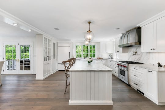 The kitchen features all white custom cabinetry with marble counter tops.