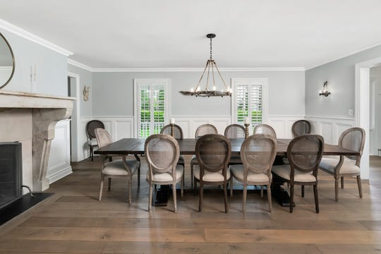 The dining room offers a antique limestone mantel and hardwood flooring.