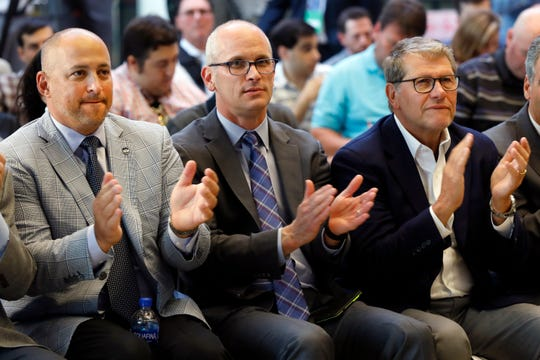 UConn Director of Athletics David Benedict, left, men's basketball coach Dan Hurley, center, and women's basketball coach Geno Auriemma applaud during the announcement that the University of Connecticut is re-joining the Big East Conference, at New York's Madison Square Garden, Thursday, June 27, 2019. (AP Photo/Richard Drew)