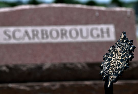 A Daughters of the American Revolution badge stands over the marker of Jewel Scarborough, in the Scarborough family plot, at the Abilene Municipal Cemetery.