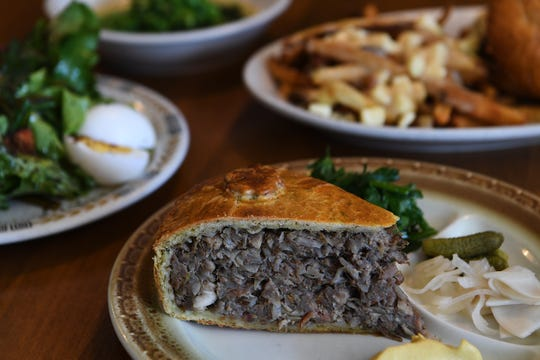The meat pie at Sawhorse is filled with pork, cabbage and leeks and served with an herb salad, mustard and pickles.
