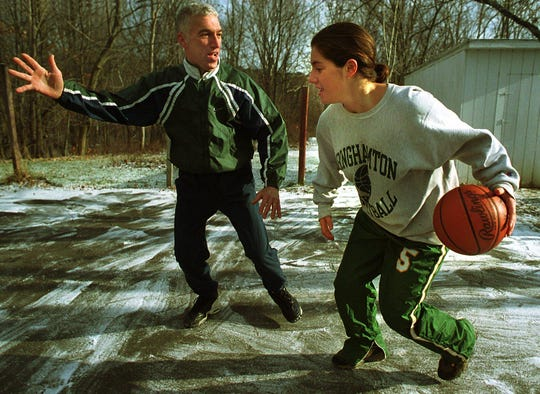 "Vestal High School basketball coach Mickey Greenberg and Binghamton University Womens basketball standout Bess Greenberg play a ""friendly"" game of one-on-one on the backyard court at their Vestal home in 1999."