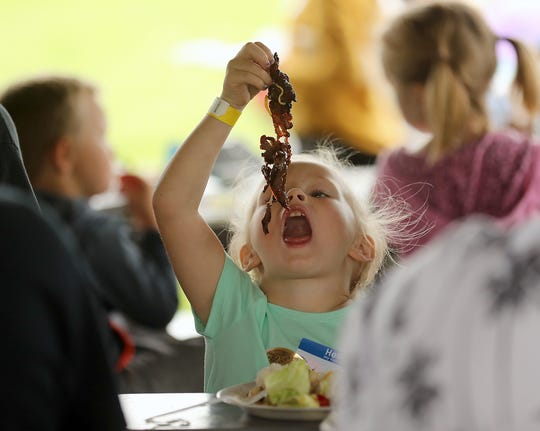 Zoey Taylor, 4, dangles a large piece of food over her mouth before father, Shane, intervened and helped her get a more bite-sized portion during the Reunification Celebration at Evergreen Rotary Park on Wednesday.