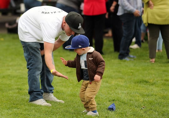 Jonathan Kaye gets a low-five from son Royce, 2, after a throw in the bean bag toss during the Reunification Celebration at Evergreen Rotary Park on Wednesday.