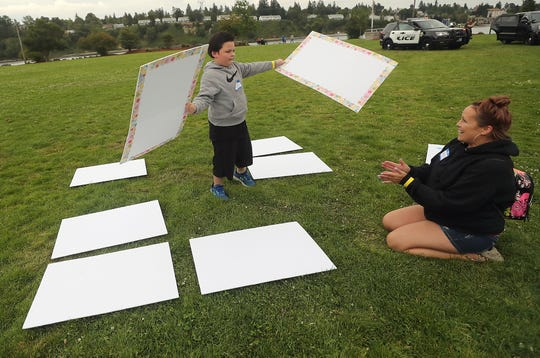 Christle Dodd applauds as son Kadus Galindo, 9, holds up a match as the two play a game of memory on the lawn during the Reunification Celebration at Evergreen Rotary Park on Wednesday.