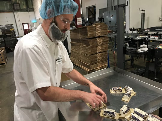 Jordan French packages goat cheese on the assembly line at Vermont Creamery in Websterville.