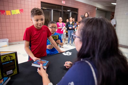 "Brothers Cristopher Martinez, left, 9, and Phillip Perez, 6, gets their copies of ""Coco"" signed by the author, Diana Lopez, following a presentation by Lopez on Thursday, June 27, 2019. Students in the Robstown Independent School District's Summer School Academy  heard from Lopez about her experience as a writer and also the importance of reading."
