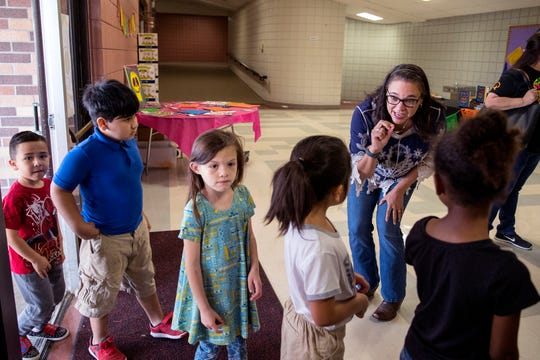 """Diana Lopez, author of """"Coco, A Story About Music, Shoes, and Family,"""" welcomes students as they arrive to hear her speak to the Robstown Independent School District's Summer School Academy students on Thursday, June 27, 2019. About 300 students heard from Lopez about her experience as a writer and also the importance of reading."""