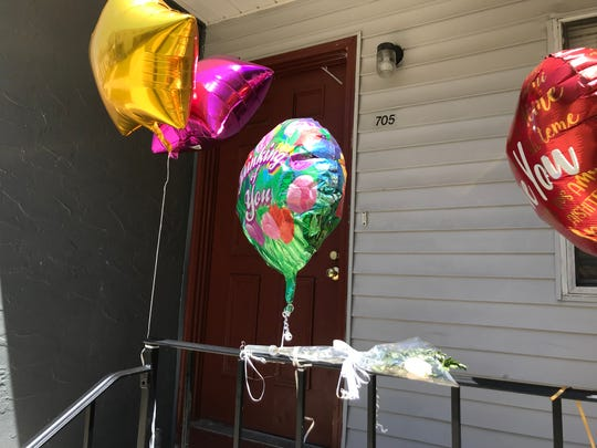 A single white rose is tied to the porch railing at the apartment where Anna Ramirez was allegedly stabbed by her twin sister, Amanda, on Saturday.