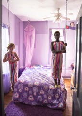 """(L-R) Charity and EV Britt stand on a hanging bed in the """"Lydia, Seller of Purple"""" themed room. Many of the rooms in the old hotel now have different themes."""