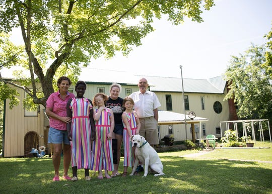 """(L-R) Becky Britt, EV Britt, Abi Britt, Lydia Britt, Charity Britt, family friend John Harris, and family dog Rufus pose in the back yard of the historical Sulphur Lick Hotel. """"It is part of the house that is nice and not as many people see,"""" said Becky Brit."""
