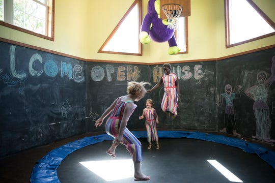 Becky Britt's daughters EV, Abi, and Charity jump up and down on the inside trampoline in the old Sulphur Lick Hotel. The trampoline was installed after rotted flooring was taken out.