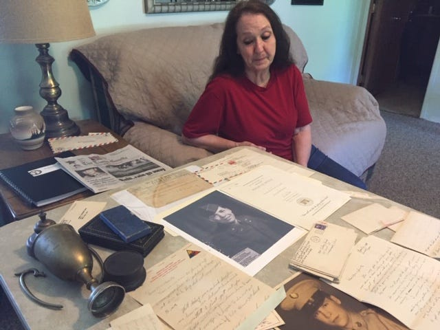 Stevie Rose looks at memorabilia for her Uncle Roger Woods who has been missing in action since 1950, presumed killed in action during the Korean War.