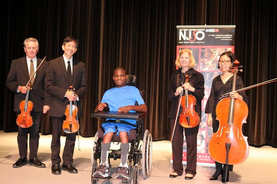 Matheny School student Jameir Warren Treadwell joins NJ Symphony Orchestra members John Connelly, James Tsao, Lucille Corwin and Hyewon Kim on the stage of the Robert Schonhorn Arts Center.