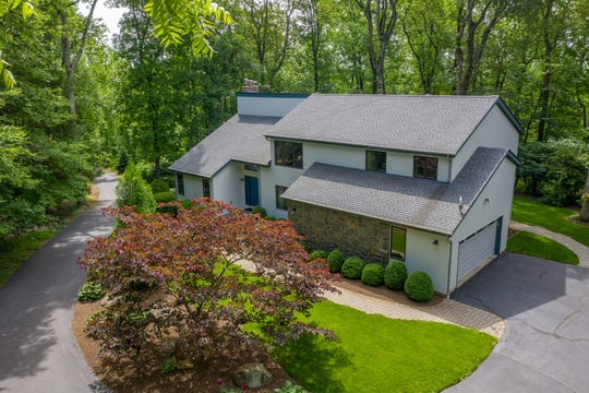 Over five level, wooded acres surround a Lebanon Township custom contemporary finished in cedar and stonework that is for sale for $499,900.