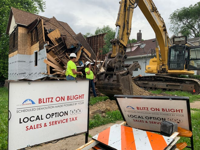A backhoe works to demolish a house on 11th Street in the Cheatom Park Neighborhood in June 2019.