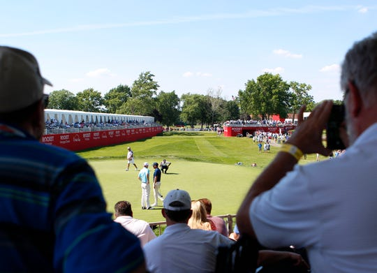 Spectators watch as golfers putt in hole 15 during the Rocket Mortgage Classic at the Detroit Golf Club in Detroit on Thursday, June 27, 2019.