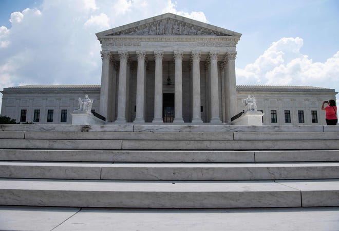 A woman takes a picture of the US Supreme Court in Washington, DC, on June 27, 2019.