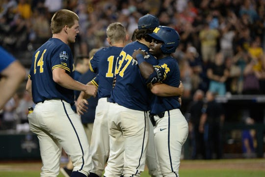 Michigan players react after losing Game 3 of the championship series against Vanderbilt in Omaha, Neb.
