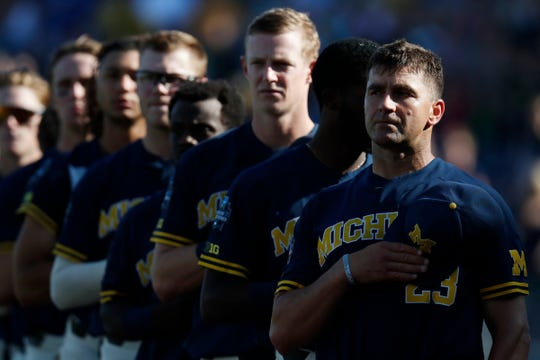 Michigan Wolverines head coach Erik Bakich, right, and his players during the national anthem prior to Game 3 of the championship series of the 2019 College World Series against Vanderbilt in Omaha, Neb., Wednesday, June 26, 2019.