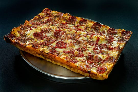 The square pizzas from Buddy's feature thick crust, crisp and caramelized edges and sauce drizzled atop the cheese.