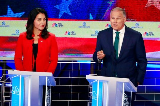 Democratic presidential candidates Washington Gov. Jay Inslee, right, speaks as Rep. Tulsi Gabbard, D-Hawaii, listens.