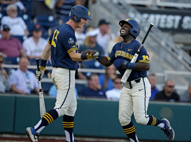 Michigan's Ako Thomas, right, and Jimmy Kerr (15) were both named to the College World Series All-Tournament team.