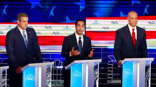 Democratic presidential candidate former Housing Secretary Julian Castro, center, speaks as Rep. Tim Ryan, D-Ohio, and Sen. Cory Booker, D-N.J., listen.