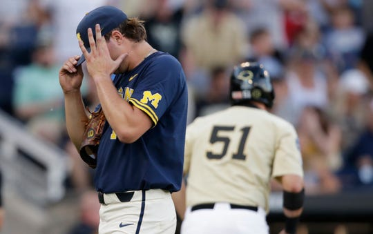 Michigan pitcher Jeff Criswell, left, adjusts his cap as he walks to the dugout after the fourth inning.