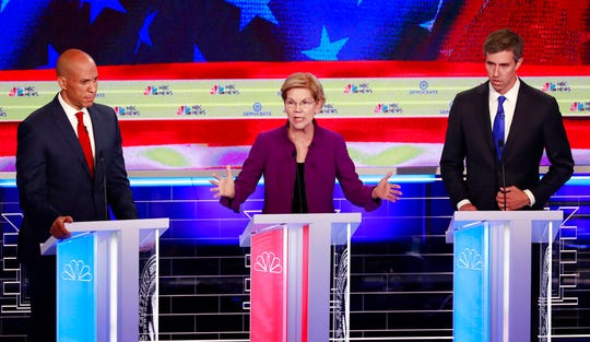 Democratic presidential candidate Sen. Elizabeth Warren, D-Mass, speaks at the Democratic primary debate hosted by NBC News at the Adrienne Arsht Center for the Performing Arts, Wednesday, June 26, 2019, in Miami, as Sen. Cory Booker, D-N.J., left and former Texas Rep. Beto O'Rourke listen.