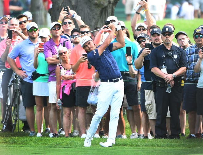 Fans cluster behind Ricky Fowler as he hits out of the rough on 6 on the first day of the Rocket Mortgage Classic in Detroit.