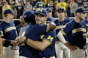 Michigan coach Erik Bakich, center, is hugged by Ako Thomas (4) as they watch Vanderbilt celebrate winning the College World Series Finals.