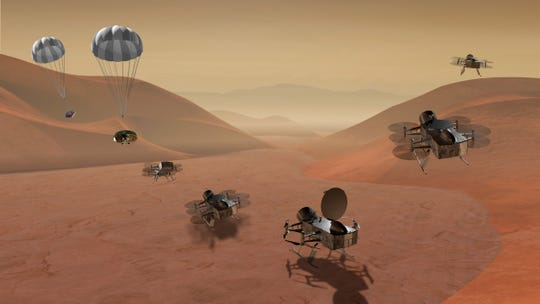 This artist's rendering made available by NASA shows multiple views of the Dragonfly dual-quadcopter lander that would take advantage of the atmosphere on Saturn's moon Titan to explore multiple locations, some hundreds of miles apart.