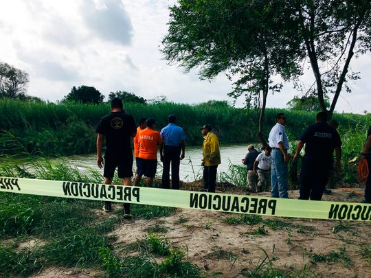 Authorities stand behind yellow warning tape along the Rio Grande bank where the bodies of Salvadoran migrant Oscar Alberto Martínez Ramírez and his nearly 2-year-old daughter Valeria were found, in Matamoros, Mexico, Monday, June 24, 2019, after they drowned trying to cross the river to Brownsville, Texas.