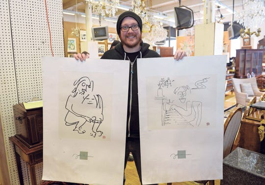 Tymias Schell, 36, of Ferndale displays his John Lennon lithograph prints.