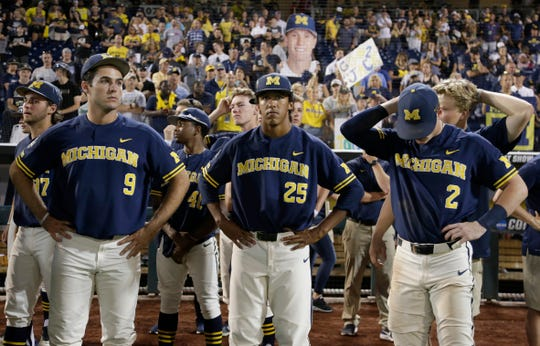 Michigan's Matthew Schmidt (9), Isaiah Paige (25) and Jack Blomgren (2) react after the Wolverines were defeated by Vanderbilt, 8-2, in Game 3 of the College World Series Finals.