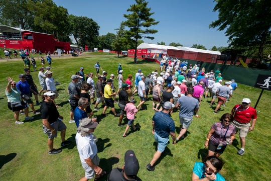 Fans cross over the course on hole 10 during the Rocket Mortgage Classic golf tournament at the Detroit Golf Club on Thursday.