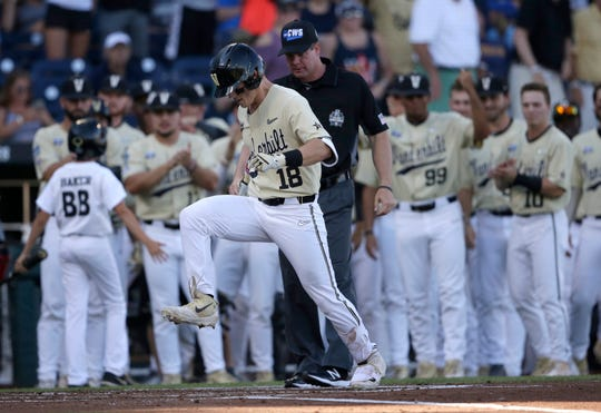 Vanderbilt's Pat DeMarco (18) stomps on home plate after hitting a home run against Michigan during the second inning.