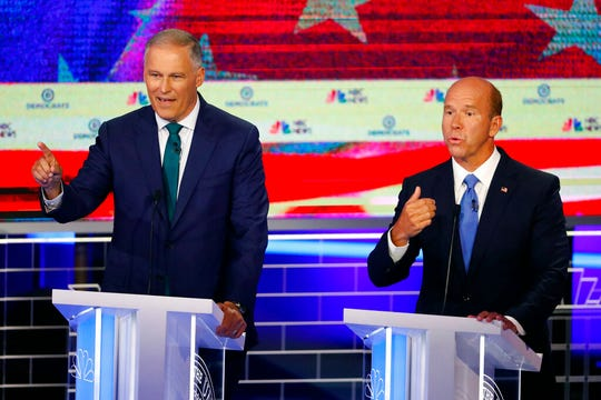 Democratic presidential candidates Washington Gov. Jay Inslee , left and former Maryland Rep. John Delaney answer a question at the same time.